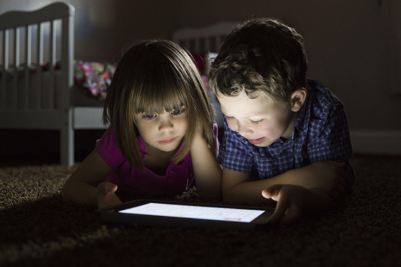 Children using digital tablet at night