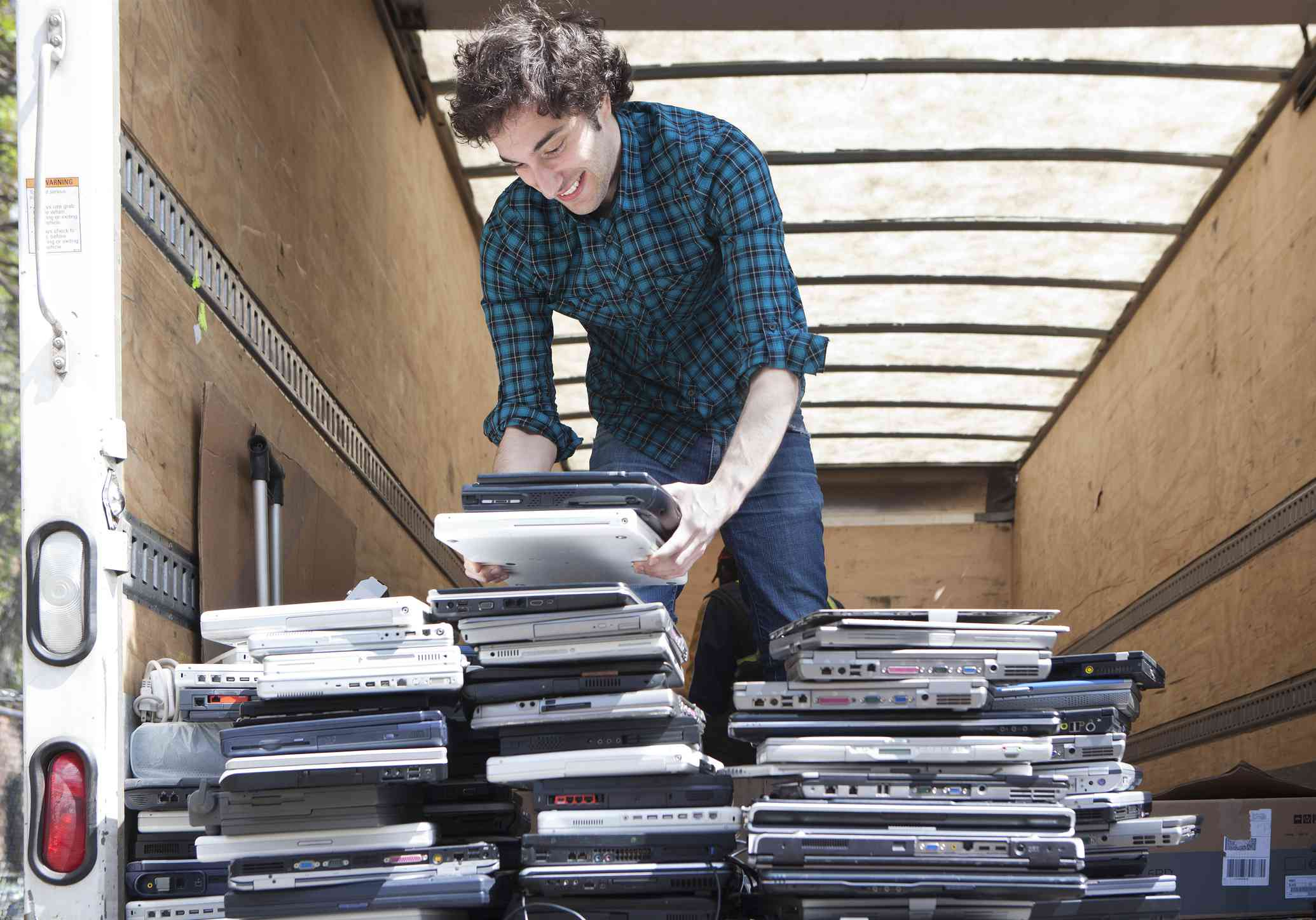 Someone moving stacks of recycled laptops.