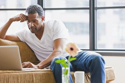 Man using laptop in loft apartment