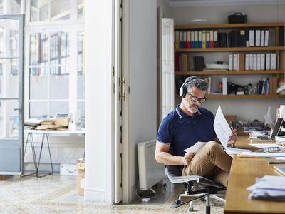 A man siting in a study with headphones on looking at paperwork