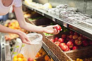 Woman selecting peaches from produce section at store