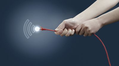 Pair of hands holding a red CAT5 Ethernet cable with a glowing connector