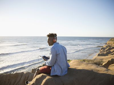Young man with headphones and digital tablet on sunny beach rocks