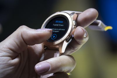 Holding a watch, tapping on the screen.