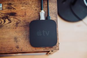 An Apple TV device sitting n the corner of a cabinet.
