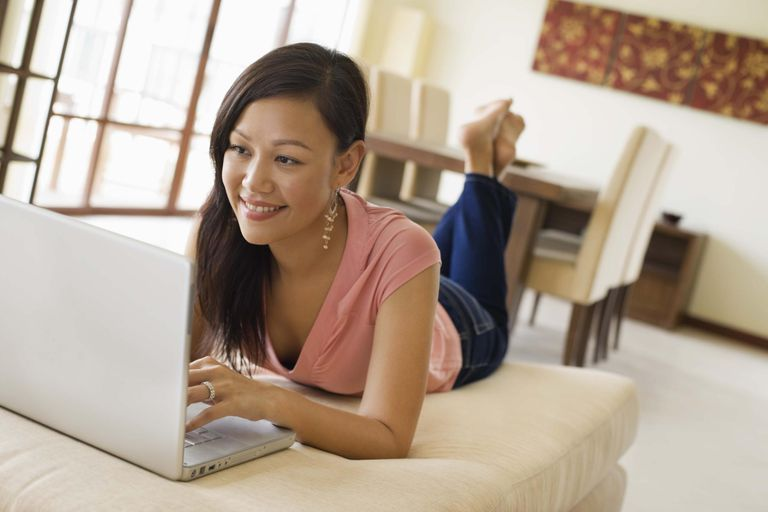 Smiling woman laying on bed with laptop