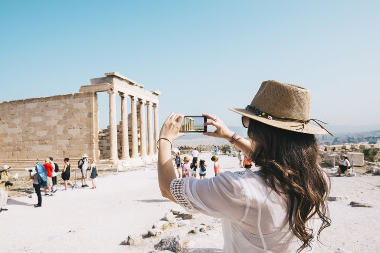 Greece, Athens, woman taking a cell phone picture of the Erechtheion temple in the Acropolis