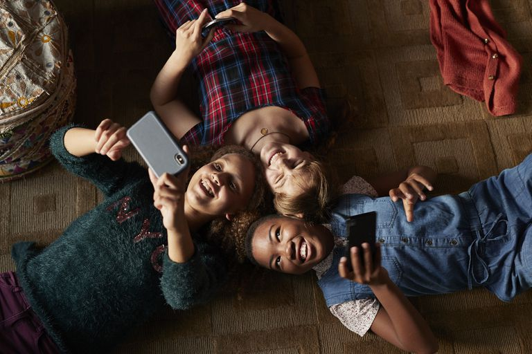 Top view of 3 tween girls laughing and looking at their smartphones