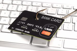 Credit card with a fish hook through it on a keyboard representing phishing credit card for information