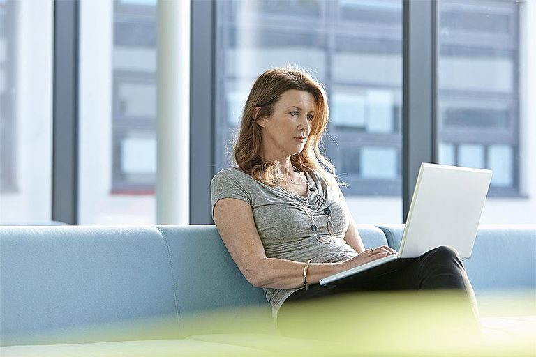 Businesswoman using a laptop on a couch