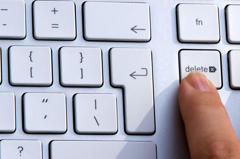 Finger pressing delete on a keyboard.