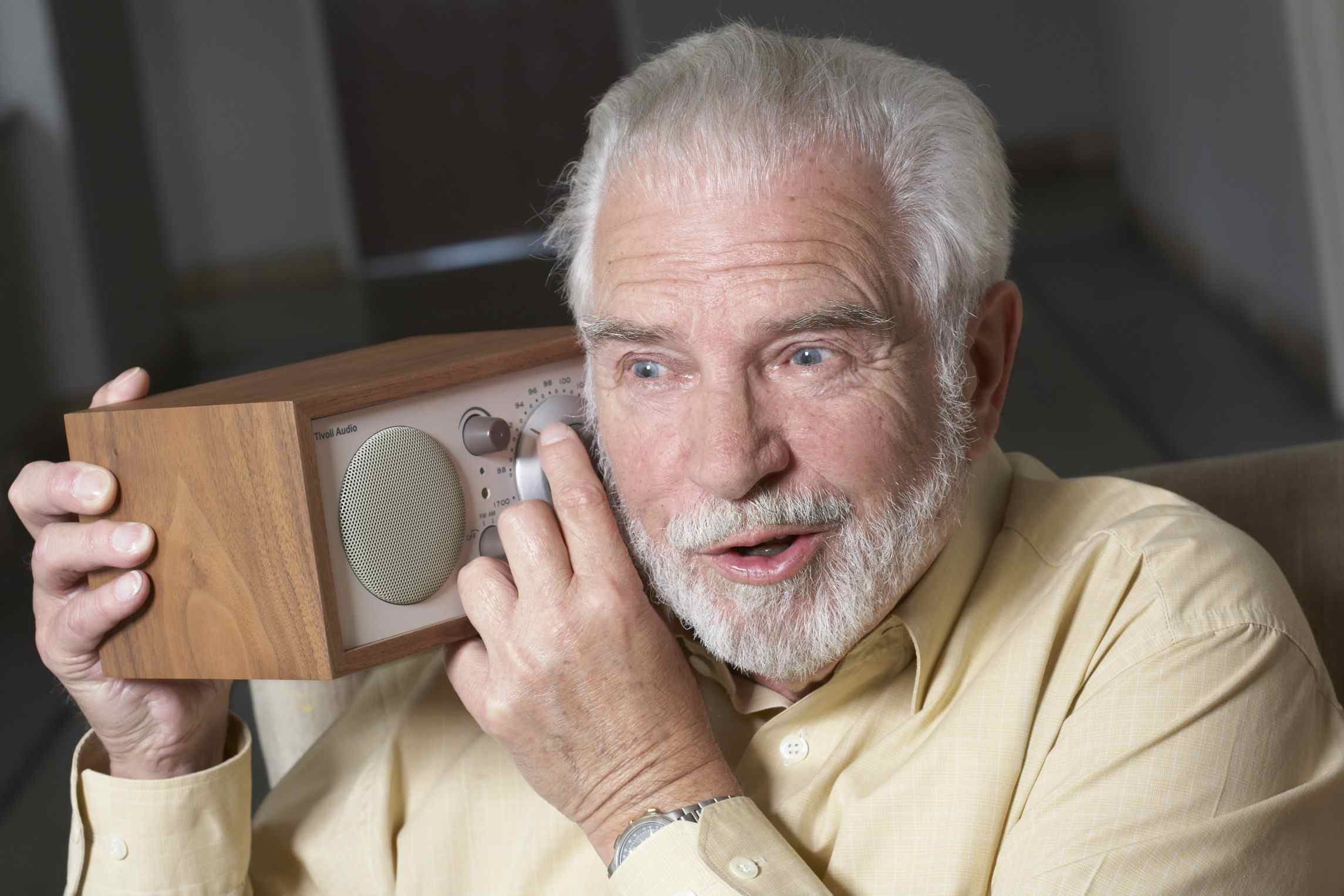 man holding radio dial up to his ear