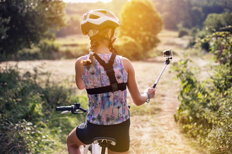Girl with helmet and a braid taking a selfie on a bicycle in a beautiful sunny day.