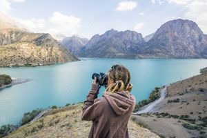 Young woman taking photos in a mountain setting