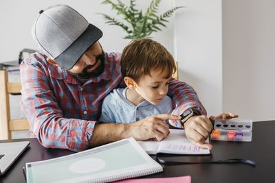 A man showing his young son how to use a smartwatch