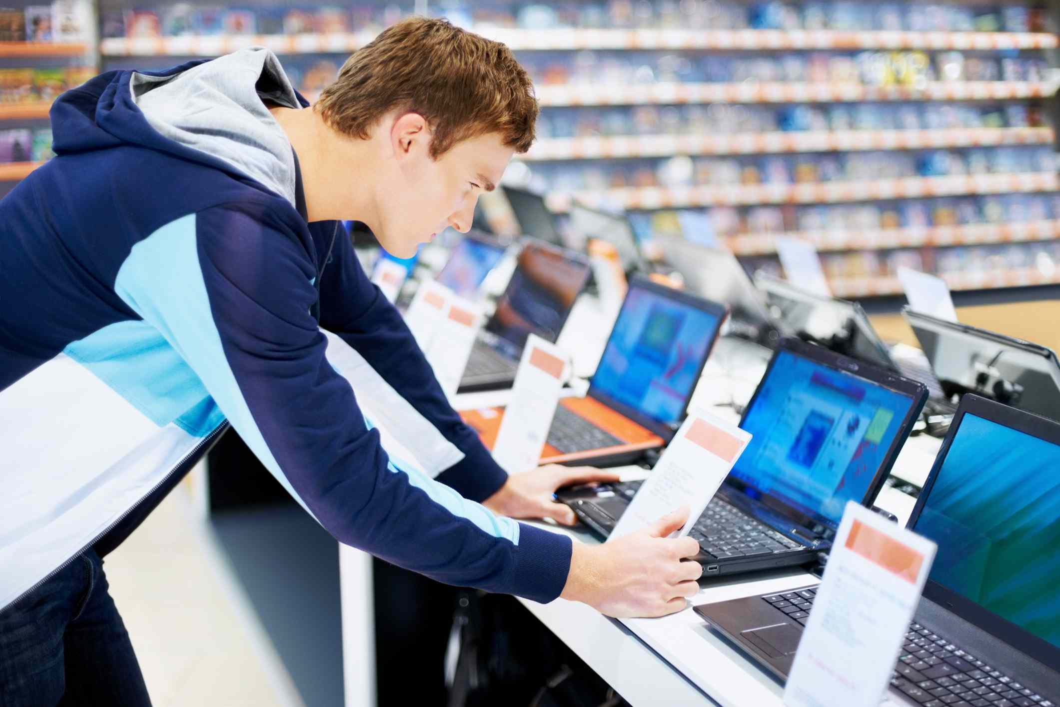 Person looking at laptops in a store.