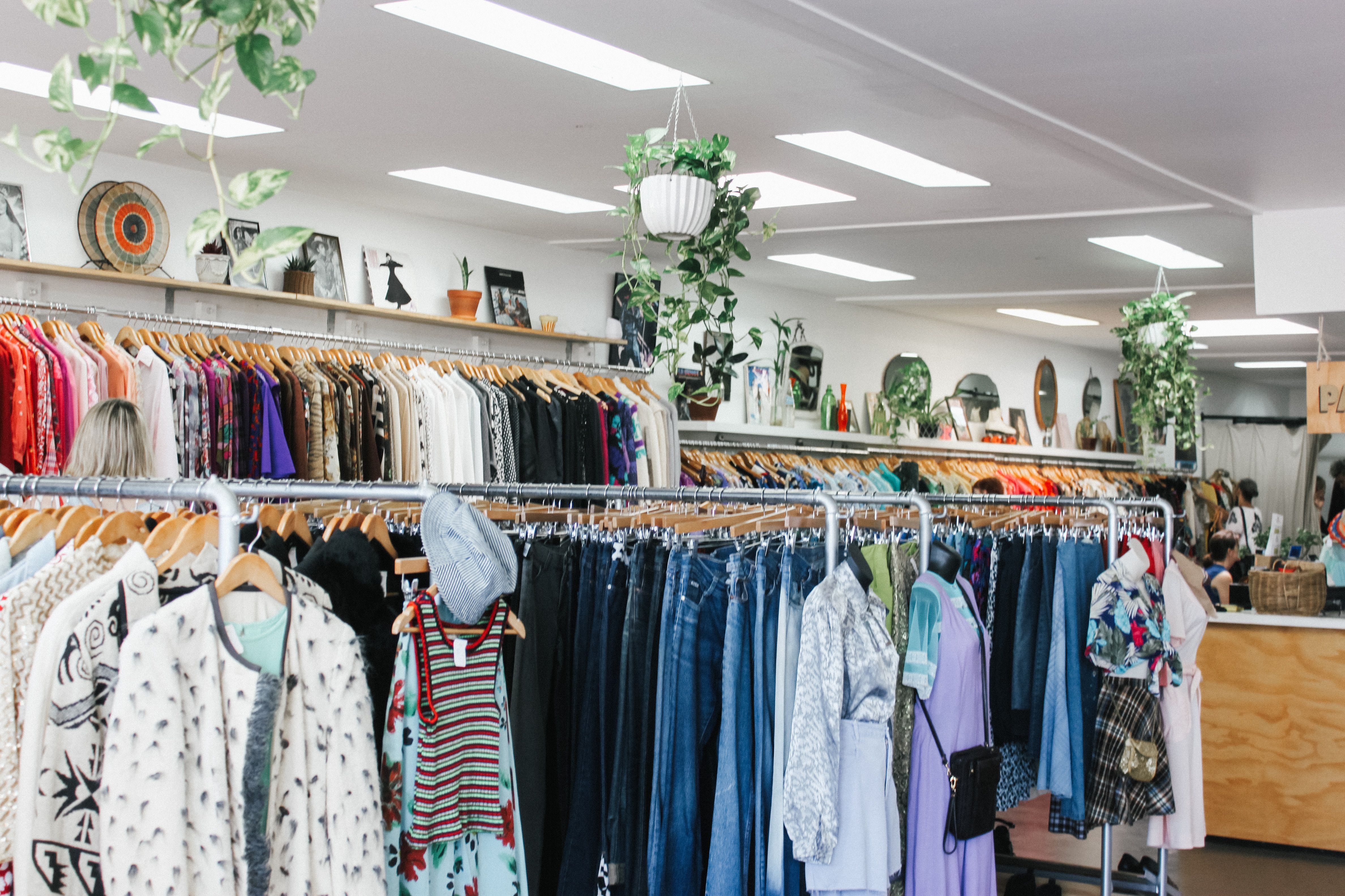 Thrift store with racks of used clothing and hanging plants