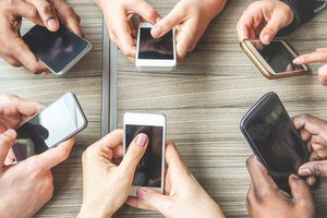 Six hands holding mobile phones in a circle