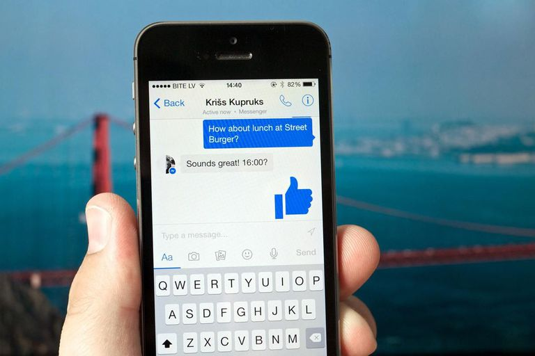 Facebook Messenger app on an iPhone held in a hand with the Golden Gate Bridge in the background