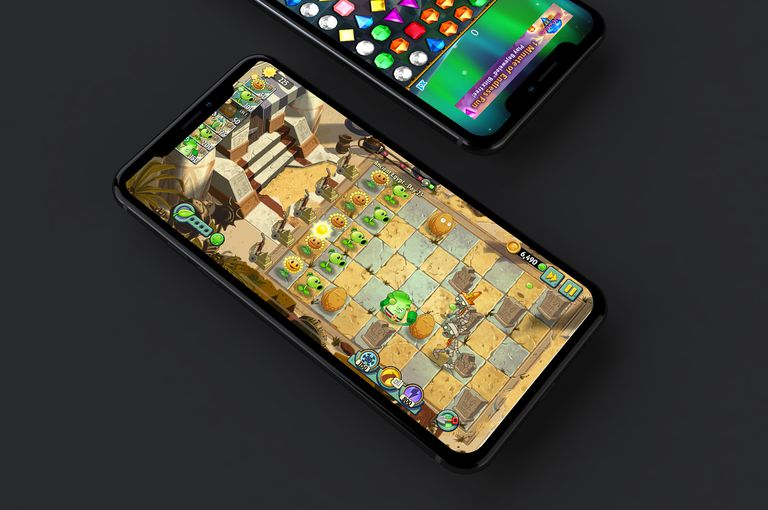 Two iPhones with Plants vs Zombies 2 and Bejeweled Classic on their screens