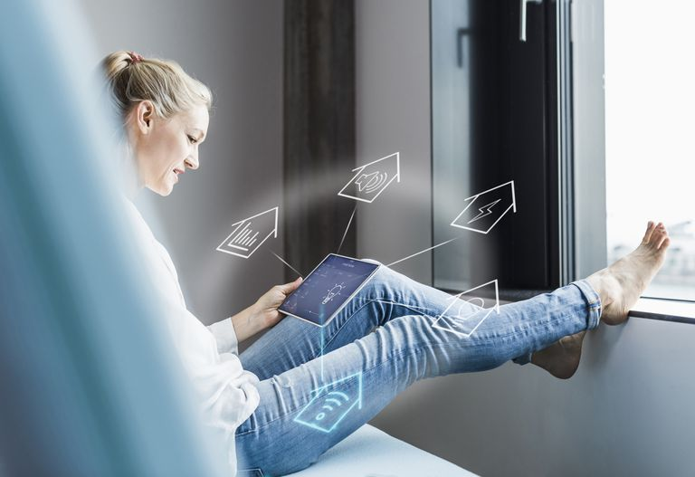 An image of a woman on her tablet at home.