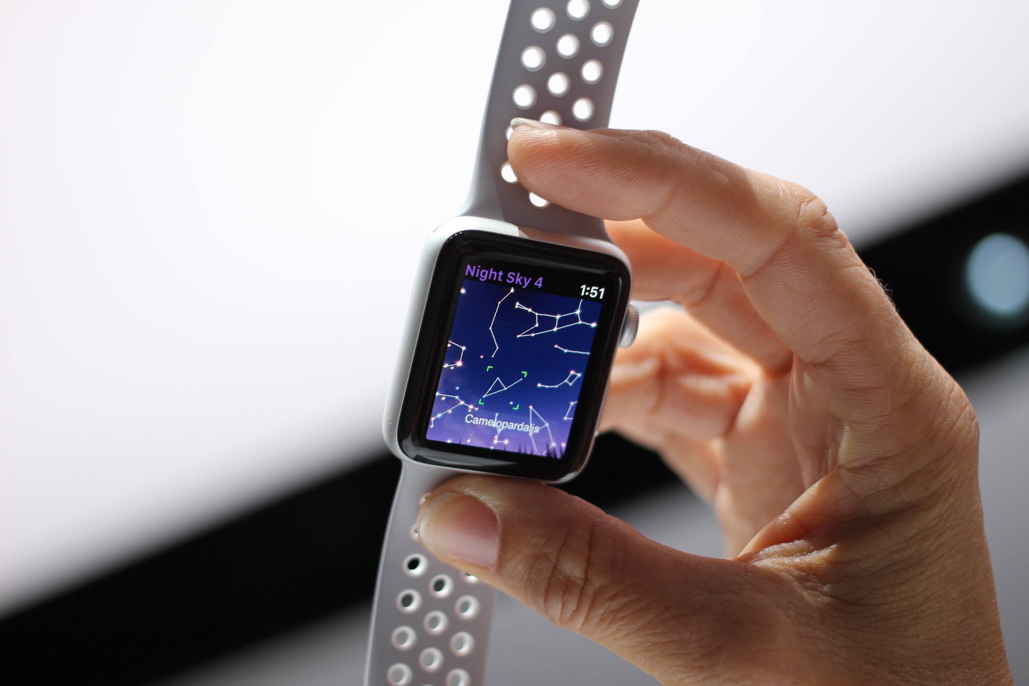 Hand holding a Nike Apple Watch with Night Sky 4 on the screen