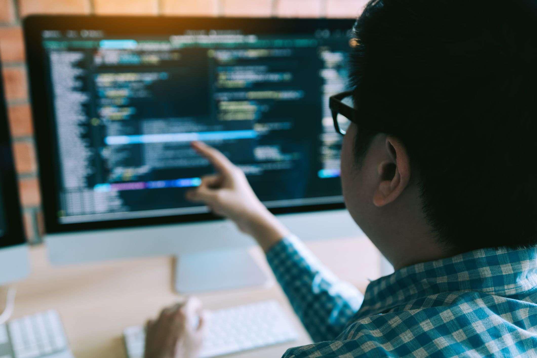 Man looking at computer code on screen