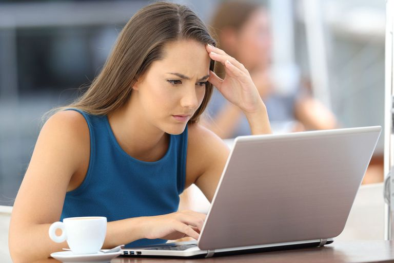 A woman looking frustrated while trying to use Facebook Marketplace on her laptop.