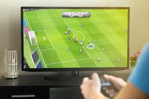 Young man hanging out and playing imaginary soccer or football video game with console and tv.