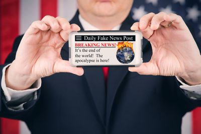 Someone displaying fake news on a smartphone with a US Flag in the background.
