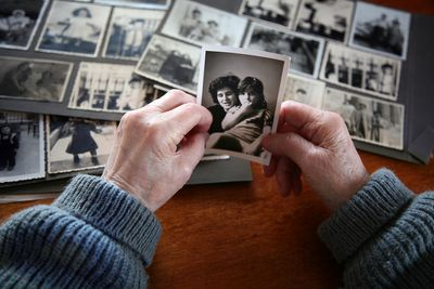 Grandparent looking at old photos of self and family