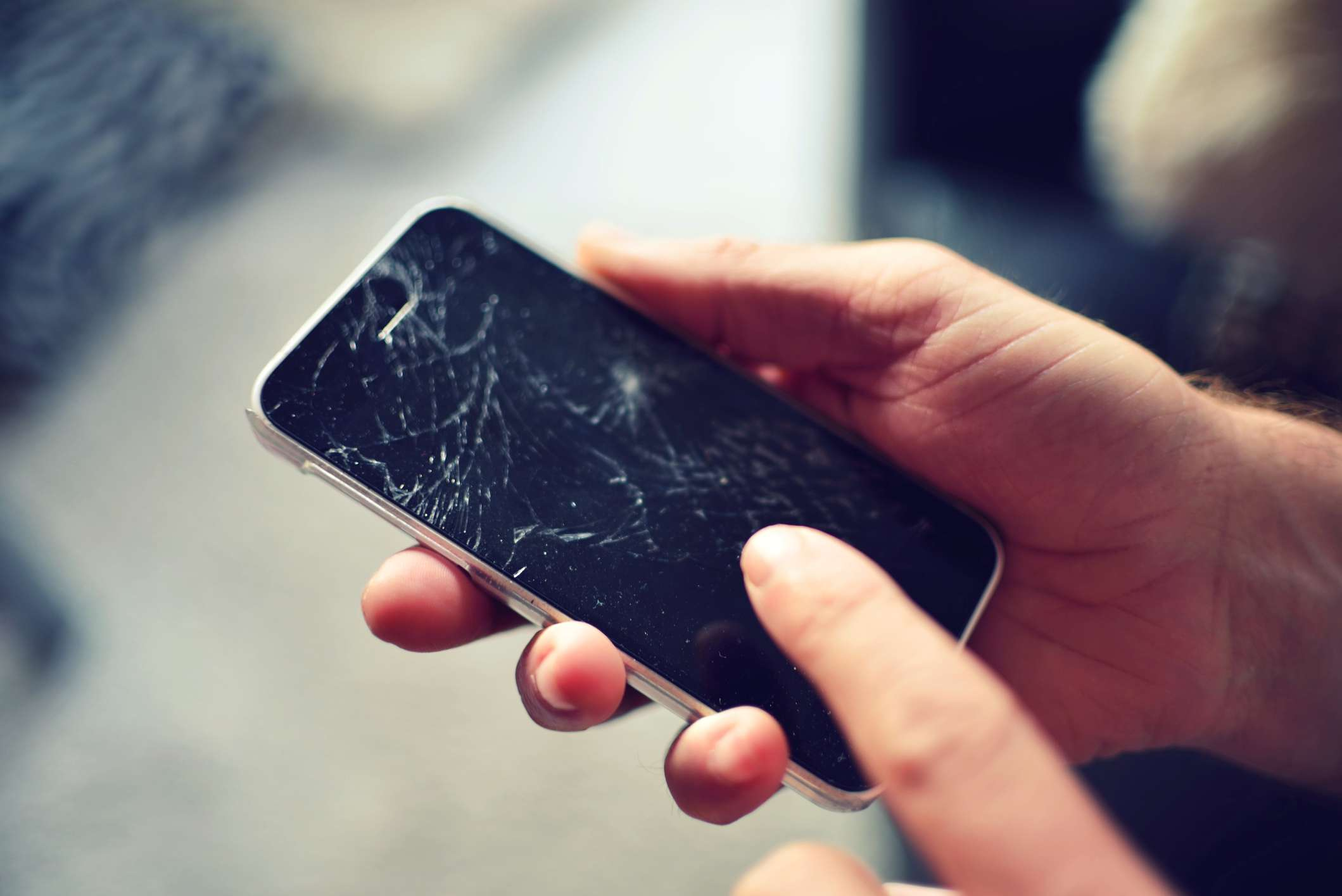Someone holding a smartphone with a broken screen.