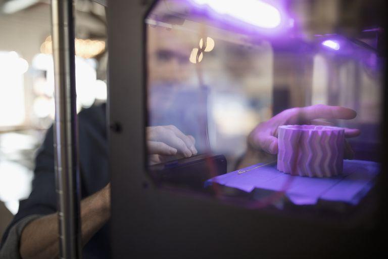 Man's hand reaching into a 3d printer
