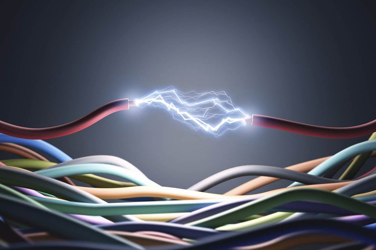 Electricity sparks between two wires depicting AC and DC currents