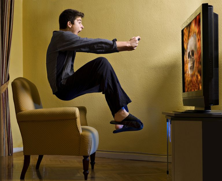 Excited man in slippers, levitating over chair, playing video game on TV