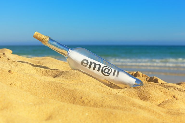 Message in a bottle on the beach that says 'email'