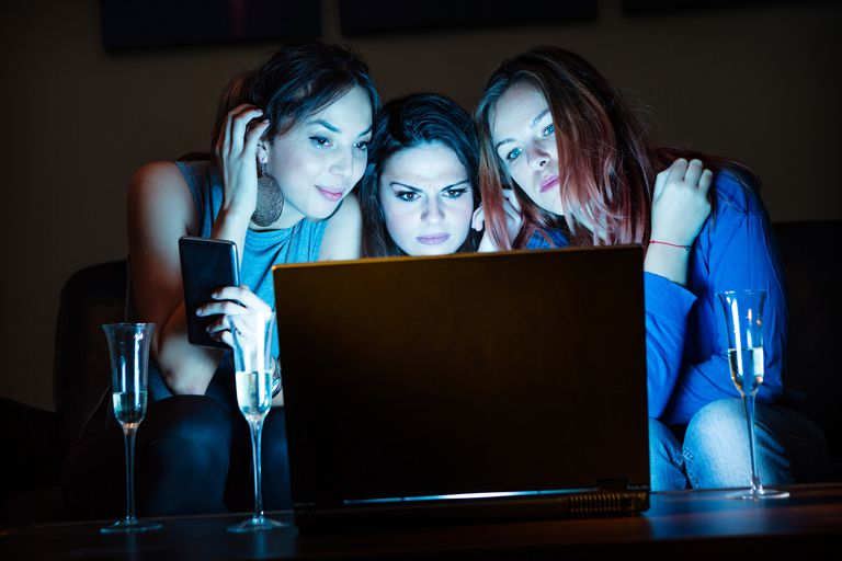 Three girlfriends, drinking champagne, watching something inter