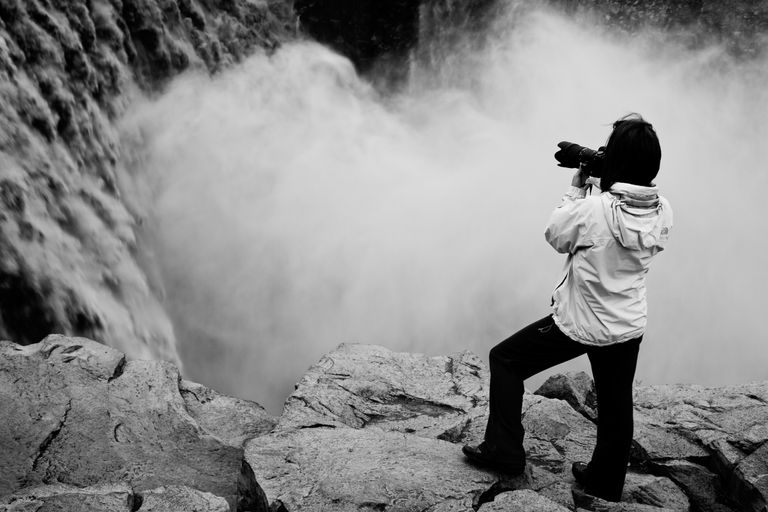 A photographer taking a picture of a waterfall in Iceland.