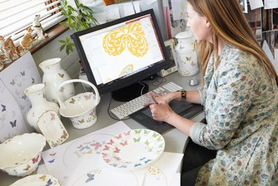 Woman doing graphic art on a computer surrounded by ceramics