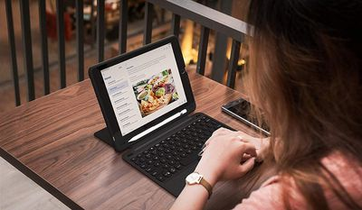 Woman at table with iPad and keyboard