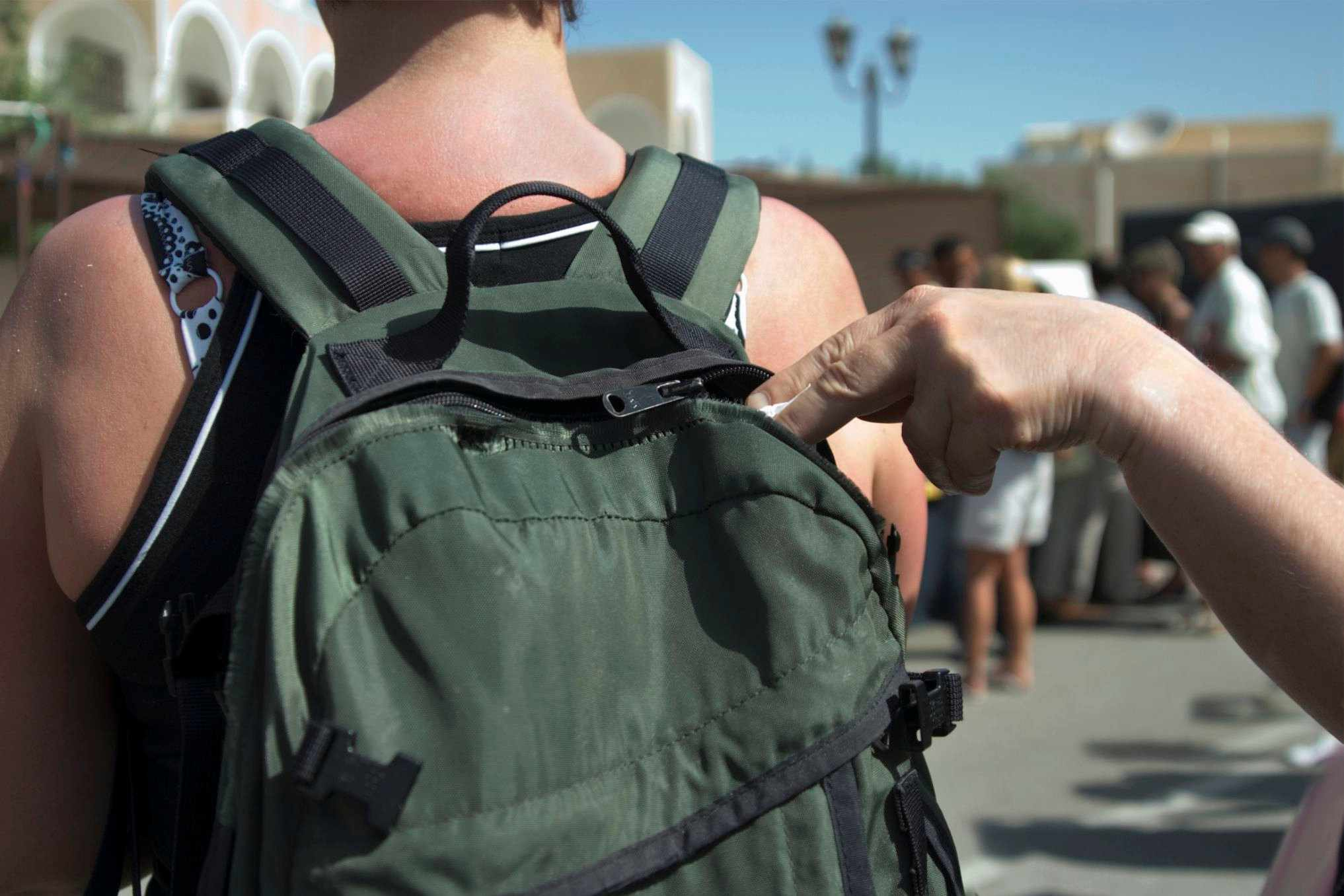 Man reaching into backpack