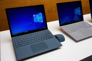 Two Microsoft Surface laptops sitting on a white table.