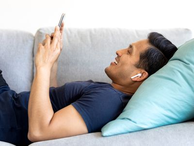 A man lying on a white couch while listening to music on his iPhone.