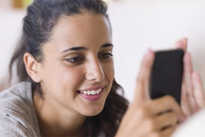 Teenage girl lying on white couch and using smart phone, close up