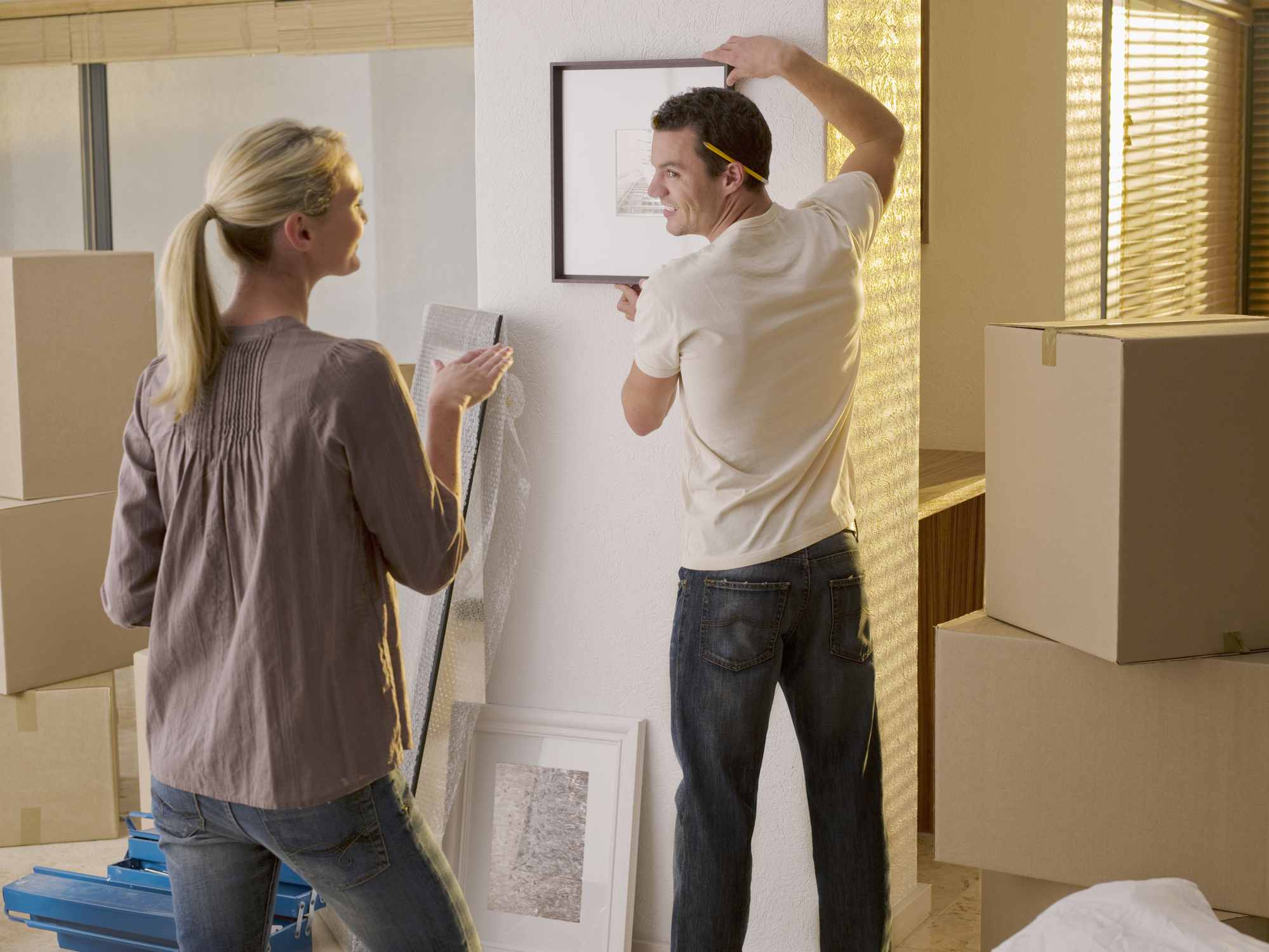 Man and woman hang up a painting on the wall.