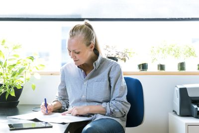 Small business owner doing paperwork in home office