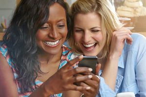 Two women becoming friends again on the Facebook social media smartphone app