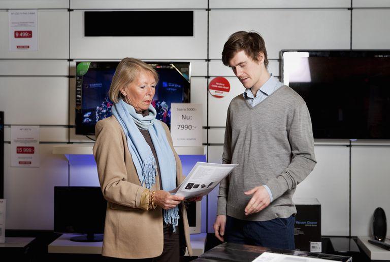 Woman asking salesman in TV store