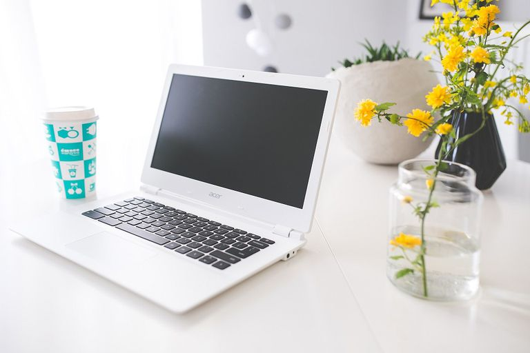 Acer Chromebook on a White Desk Next to a Reusable Coffee Cub and a Vase