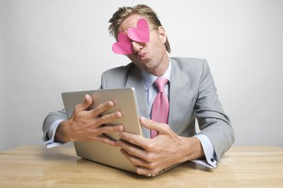 Guy in suit with pink tie and hearts for eyes embracing a laptop